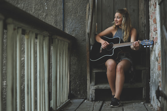 A young woman playing guitar sitting on some stairs